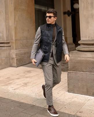 Dunkelbraune Leder niedrige Sneakers kombinieren – 205 Herren Outfits: Paaren Sie eine dunkelblaue gesteppte ärmellose Jacke mit einem grauen Anzug, um vor Klasse und Perfektion zu strotzen. Dunkelbraune Leder niedrige Sneakers verleihen einem klassischen Look eine neue Dimension.