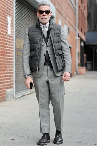 50 Jährige: Dunkelgraue gesteppte ärmellose Jacke kombinieren – 4 Herren Outfits: Erwägen Sie das Tragen von einer dunkelgrauen gesteppten ärmelloser Jacke und einem grauen Anzug für einen stilvollen, eleganten Look. Komplettieren Sie Ihr Outfit mit schwarzen Leder Derby Schuhen, um Ihr Modebewusstsein zu zeigen.