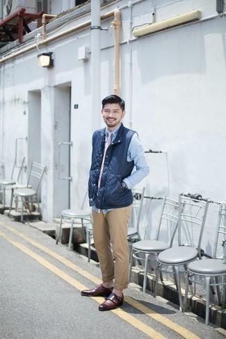 Beige Chinohose kombinieren: trends 2020: Entscheiden Sie sich für eine dunkelblaue gesteppte ärmellose Jacke und eine beige Chinohose für ein sonntägliches Mittagessen mit Freunden. Fühlen Sie sich ideenreich? Vervollständigen Sie Ihr Outfit mit dunkelroten Doppelmonks aus Leder.