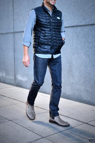 Wie kombinieren: dunkelblaue gesteppte ärmellose Jacke, hellblaues Jeanshemd, dunkelblaue Jeans, graue Chelsea-Stiefel aus Wildleder