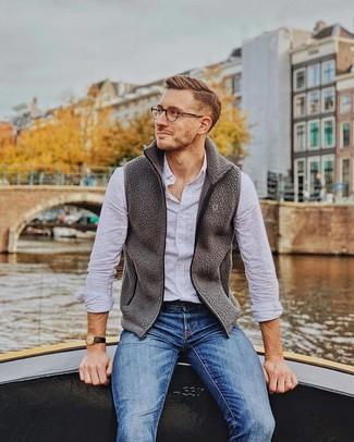 Wie kombinieren: dunkelgraue Fleece-ärmellose Jacke, weißes Langarmhemd, blaue Jeans, schwarze Lederuhr