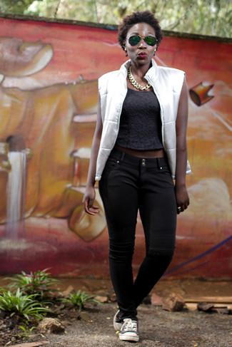 Wie kombinieren: weiße ärmellose Jacke, schwarzes kurzes Oberteil, schwarze Chinohose, schwarze und weiße niedrige Sneakers