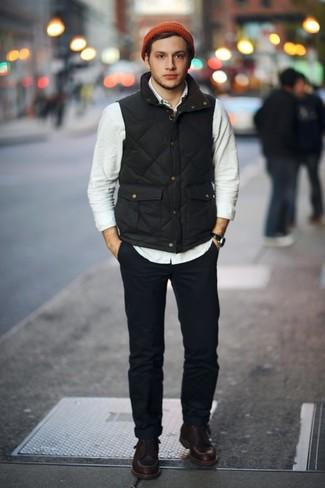 Wie kombinieren: schwarze ärmellose Jacke, hellbeige Langarmhemd, dunkelblaue Chinohose, dunkelbraune Lederarbeitsstiefel