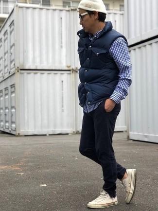Wie kombinieren: dunkelblaue gesteppte ärmellose Jacke, dunkelblaues und weißes Langarmhemd mit Vichy-Muster, schwarze Kordjeans, weiße Segeltuch niedrige Sneakers