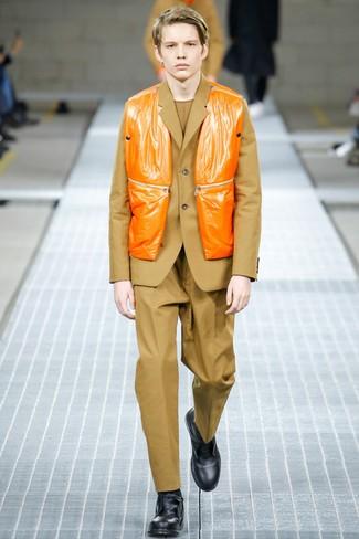 orange ärmellose Jacke, beige Anzug, beige Pullover mit einem Rundhalsausschnitt, schwarze Lederfreizeitstiefel für Herren
