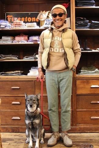 Wie kombinieren: hellbeige gesteppte ärmellose Jacke, beige bedruckter Pullover mit einem Kapuze, olivgrüne Chinohose, graue Chukka-Stiefel aus Wildleder