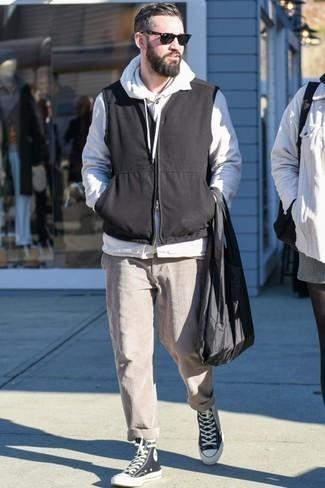 Schwarze ärmellose Jacke kombinieren: trends 2020: Vereinigen Sie eine schwarze ärmellose Jacke mit einer hellbeige Cord Chinohose für ein sonntägliches Mittagessen mit Freunden. Fühlen Sie sich ideenreich? Vervollständigen Sie Ihr Outfit mit schwarzen und weißen hohen Sneakers aus Segeltuch.