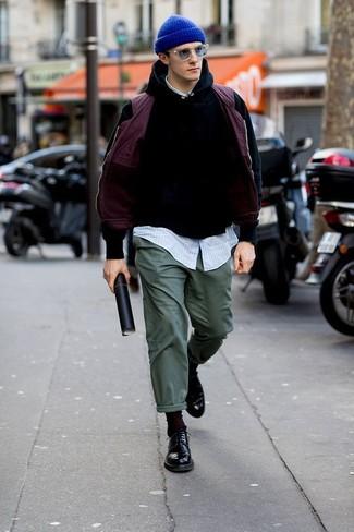 Wie kombinieren: lila ärmellose Jacke, schwarzer Pullover mit einem Kapuze, hellblaues vertikal gestreiftes Langarmhemd, dunkelgrüne Chinohose
