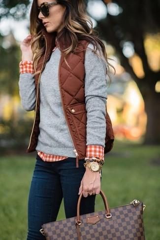 Wie kombinieren: braune gesteppte ärmellose Jacke, grauer Pullover mit einem Rundhalsausschnitt, rotes und weißes Businesshemd mit Vichy-Muster, dunkelblaue enge Jeans