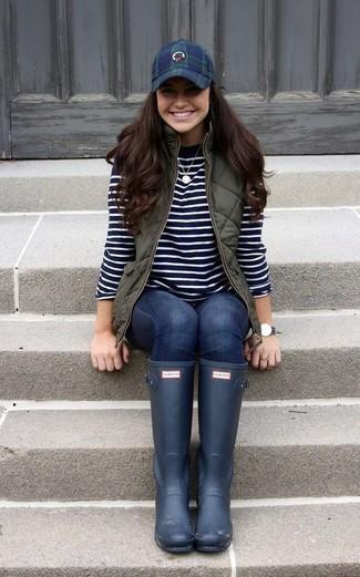Wie kombinieren: olivgrüne gesteppte ärmellose Jacke, schwarzer und weißer horizontal gestreifter Pullover mit einem Rundhalsausschnitt, dunkelblaue enge Jeans, dunkelblaue Gummistiefel
