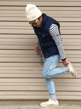 Wie kombinieren: dunkelblaue gesteppte ärmellose Jacke, weißer und dunkelblauer horizontal gestreifter Pullover mit einem Rundhalsausschnitt, hellblaue Jeans, weiße niedrige Sneakers
