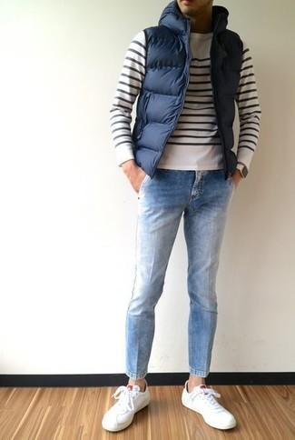 Wie kombinieren: dunkelblaue gesteppte ärmellose Jacke, weißer und schwarzer horizontal gestreifter Pullover mit einem Rundhalsausschnitt, hellblaue Jeans, weiße Leder niedrige Sneakers