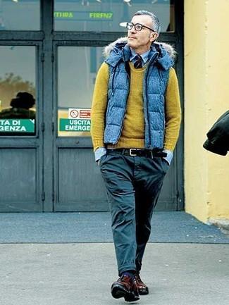 Wie kombinieren: blaue gesteppte ärmellose Jacke, olivgrüner Pullover mit einem Rundhalsausschnitt, hellblaues Jeanshemd, schwarze Chinohose