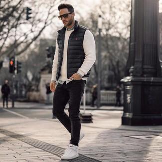 Wie kombinieren: schwarze ärmellose Jacke, weißer Pullover mit einem Rundhalsausschnitt, hellblaues Jeanshemd, schwarze enge Jeans