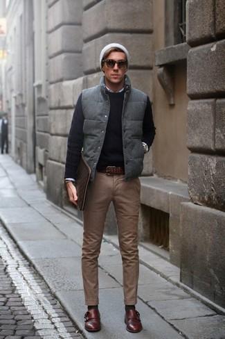 Wie kombinieren: graue gesteppte ärmellose Jacke, schwarzer Pullover mit einem Rundhalsausschnitt, weißes Langarmhemd, braune Chinohose