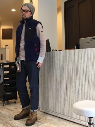 Wie kombinieren: dunkelblaue Fleece-ärmellose Jacke, hellbeige Pullover mit einem Rundhalsausschnitt, graues Langarmshirt, dunkelblaue Jeans