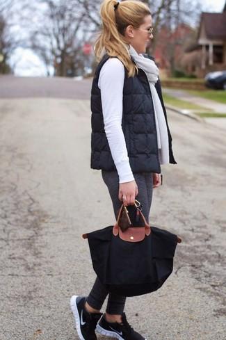 Dunkelgraue Leggings kombinieren: trends 2020: Wenn Sie auf der Suche nach dem idealen Wochenend-Stil sind, paaren Sie eine schwarze gesteppte ärmellose Jacke mit dunkelgrauen Leggings. Suchen Sie nach leichtem Schuhwerk? Wählen Sie schwarzen Sportschuhe für den Tag.