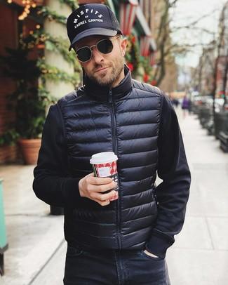 Wie kombinieren: schwarze ärmellose Jacke, schwarzes Sweatshirt, schwarze Jeans, schwarze und weiße bedruckte Baseballkappe
