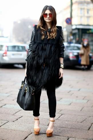 Wie kombinieren: schwarzer Pelz ärmelloser Mantel, schwarze Leder Bomberjacke, schwarze enge Jeans, beige klobige Leder Sandaletten