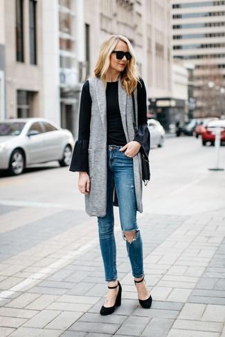 Wie kombinieren: grauer ärmelloser Mantel, schwarzes Langarmshirt mit Rüschen, blaue enge Jeans mit Destroyed-Effekten, schwarze Keilpumps aus Wildleder