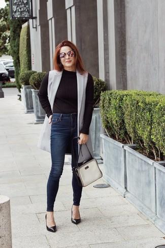 Wie kombinieren: grauer ärmelloser Mantel, schwarzer Pullover mit einem Rundhalsausschnitt, dunkelblaue enge Jeans, schwarze Leder Pumps