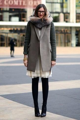 Dunkelgrüne Strickjacke kombinieren – 32 Damen Outfits: Probieren Sie diese Paarung aus einer dunkelgrünen Strickjacke und einem grauen ärmellosem Mantel, um einen zeitgenössischen Freizeit-Look zu schaffen. Vervollständigen Sie Ihr Look mit schwarzen Leder Stiefeletten.