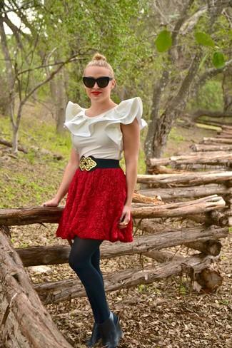 Wie kombinieren: weißes ärmelloses Oberteil aus Seide, roter ausgestellter Rock mit Reliefmuster, schwarze Keilstiefeletten aus Leder, schwarzer und goldener elastischer Taillengürtel