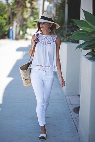 Wie kombinieren: weißes ärmelloses Oberteil aus Häkel, weiße enge Jeans, weiße und schwarze Espadrilles, hellbeige Shopper Tasche aus Stroh