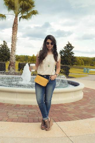 Wie kombinieren: hellbeige besticktes ärmelloses Oberteil, blaue Jeans, braune Keilsandaletten aus Leder, senf Leder Umhängetasche