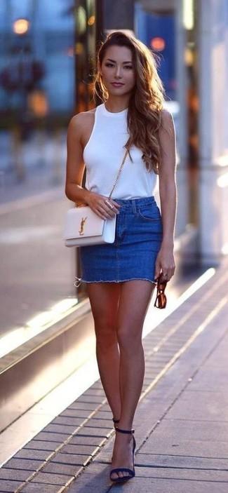 Wie kombinieren: weißes ärmelloses Oberteil, blauer Jeans Minirock, dunkelblaue Wildleder Sandaletten, weiße Leder Umhängetasche