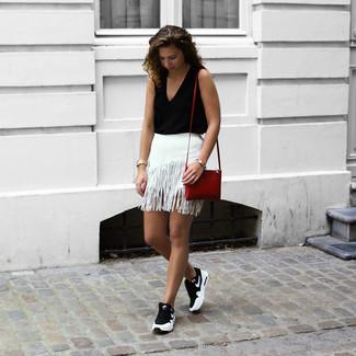 Wie kombinieren: schwarzes ärmelloses Oberteil, weißer Fransen Minirock, schwarze und weiße Sportschuhe, rote Leder Umhängetasche