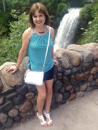 blaues bedrucktes ärmelloses Oberteil, schwarze Shorts, weiße Keilsandaletten aus Leder, weiße Leder Umhängetasche für Damen