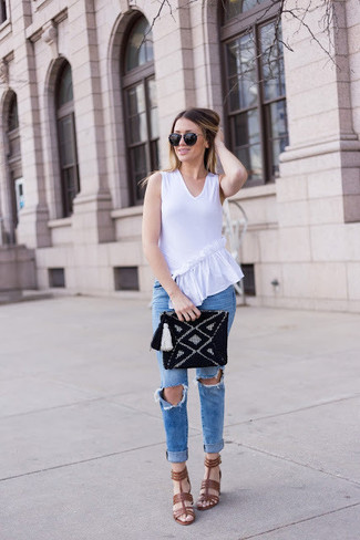Wie kombinieren: weißes ärmelloses Oberteil mit Rüschen, blaue enge Jeans mit Destroyed-Effekten, braune Leder Sandaletten, schwarze Strick Clutch