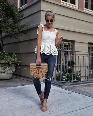 Wie kombinieren: weißes ärmelloses Oberteil aus Spitze, dunkelblaue enge Jeans mit Destroyed-Effekten, beige Leder Sandaletten, beige Stroh Clutch