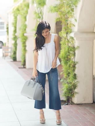 Dunkelblauen Hosenrock aus Jeans kombinieren – 5 Sommer Damen Outfits: Um einen unkompliziertfen aber modischen Alltags-Look zu schaffen, probieren Sie diese Paarung aus einem weißen ärmellosem Oberteil und einem dunkelblauen Hosenrock aus Jeans. Fühlen Sie sich ideenreich? Entscheiden Sie sich für hellbeige Keilsandaletten aus Leder. So einfach kann ein cooles Sommer-Outfit sein.