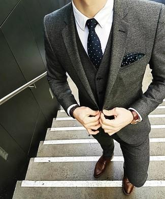 Wie kombinieren: grauer Wollanzug, weißes Businesshemd, braune Leder Brogues, schwarze und weiße gepunktete Krawatte