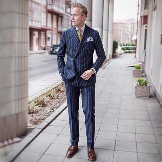 Wie kombinieren: dunkelblauer vertikal gestreifter Anzug, weißes Businesshemd, braune Leder Brogues, gelbe bedruckte Krawatte