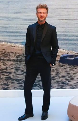 Wie kombinieren: schwarzer Anzug, schwarzes Businesshemd, schwarze Chelsea-Stiefel aus Leder, schwarze Fliege