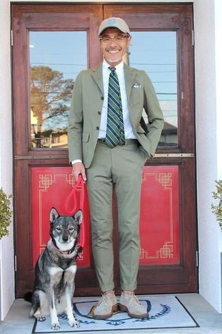 Wie kombinieren: olivgrüner Anzug, weißes Businesshemd, olivgrüne Chukka-Stiefel aus Segeltuch, hellbeige Baseballkappe