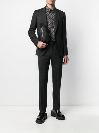 Wie kombinieren: schwarzer Anzug, schwarzes und weißes bedrucktes Businesshemd, schwarze klobige Leder Derby Schuhe, schwarze Leder Bauchtasche