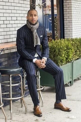 Mode für Herren ab 30 2020: Paaren Sie einen dunkelblauen vertikal gestreiften Anzug mit einem weißen Businesshemd für eine klassischen und verfeinerte Silhouette. Beige Monks aus Leder sind eine gute Wahl, um dieses Outfit zu vervollständigen.