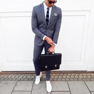 Wie kombinieren: dunkelgrauer Anzug, weißes Businesshemd, weiße niedrige Sneakers, schwarze Leder Aktentasche