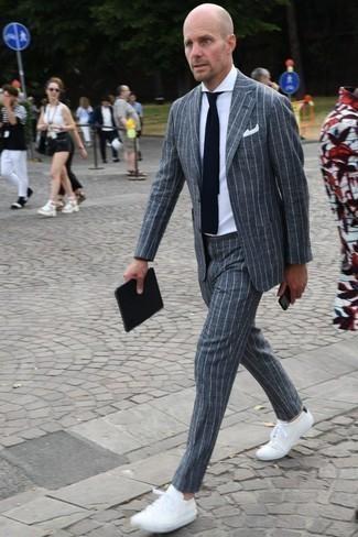 Dunkelblaue und weiße Strick Krawatte kombinieren: trends 2020: Entscheiden Sie sich für einen klassischen Stil in einem grauen vertikal gestreiften Anzug und einer dunkelblauen und weißen Strick Krawatte. Weiße niedrige Sneakers liefern einen wunderschönen Kontrast zu dem Rest des Looks.