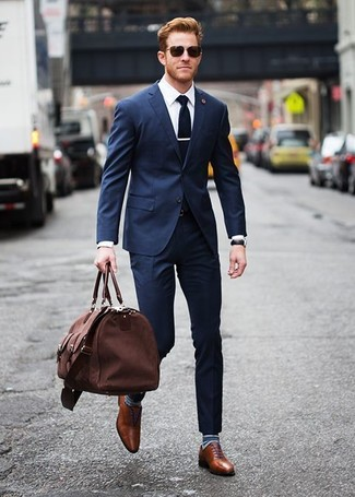 Wie kombinieren: dunkelblauer Anzug, weißes Businesshemd, braune Leder Oxford Schuhe, braune Segeltuch Reisetasche