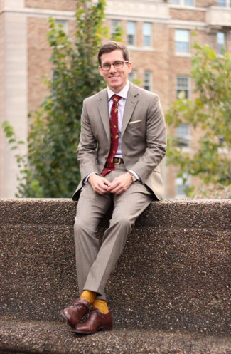 Wie kombinieren: grauer Anzug, weißes Businesshemd, braune Leder Oxford Schuhe, rote bedruckte Krawatte
