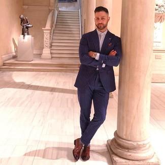 Wie kombinieren: dunkelblauer vertikal gestreifter Anzug, hellviolettes Businesshemd, braune Leder Oxford Schuhe, mehrfarbiges bedrucktes Einstecktuch
