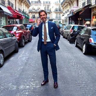 Wie kombinieren: dunkelblauer vertikal gestreifter Anzug, weißes Businesshemd, dunkelbraune Leder Slipper, braune Strick Krawatte