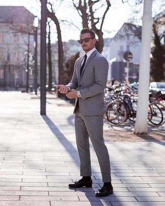 Wie kombinieren: grauer Anzug, weißes Businesshemd, schwarze Leder Slipper mit Quasten, schwarze Krawatte