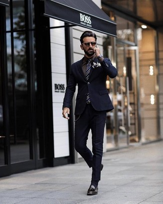 Herren Outfits 2020: Kombinieren Sie einen dunkelblauen Anzug mit einer dunkelbraunen Anzughose, um vor Klasse und Perfektion zu strotzen. Wenn Sie nicht durch und durch formal auftreten möchten, vervollständigen Sie Ihr Outfit mit dunkelbraunen Leder Slippern mit Quasten.