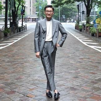 Weißes T-Shirt mit einem Rundhalsausschnitt kombinieren – 53 Elegante Herren Outfits: Erwägen Sie das Tragen von einem weißen T-Shirt mit einem Rundhalsausschnitt und einem grauen Anzug für Drinks nach der Arbeit. Schwarze Leder Slipper mit Quasten sind eine einfache Möglichkeit, Ihren Look aufzuwerten.